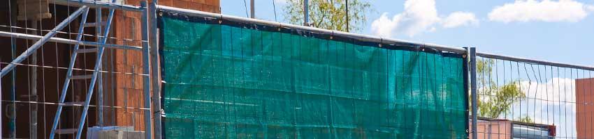 Ein mit grünem Sichtschutz bespannter Bauzaun auf einer Baustelle