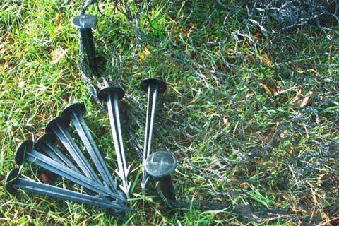 Teichnetz auf Wiese am Teichrand ausgelegt und mit Erdspiessen im Boden fixiert