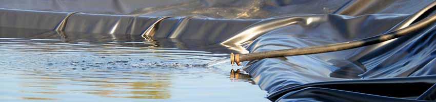 ein mit schwarzer teichfolie ausgelegter Teich wird mit wasser befüllt